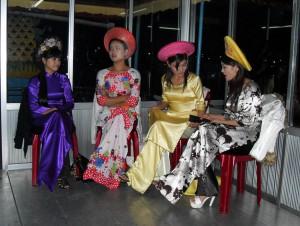 Vietnamesinnen sitzen und machen Pause vor ihrem nächsten musikalischen Auftritt