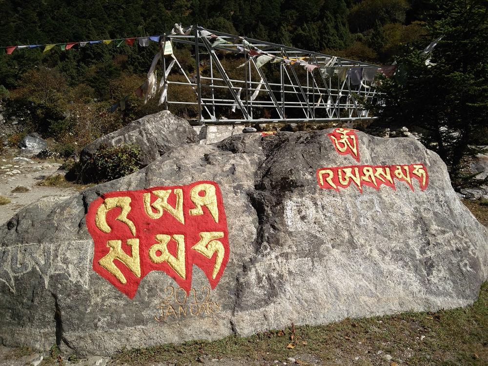 Rot-goldene Sanskrit-Zeichen auf Fels in Nepal